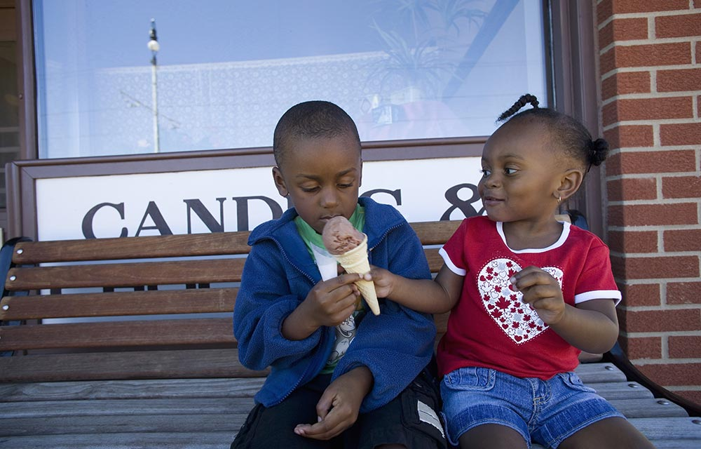 Empathetic little girl sharing ice cream to a young boy